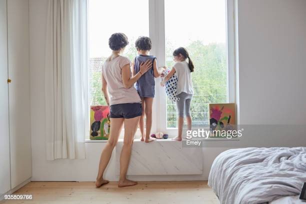 Mother, son and daughter looking out of bedroom window, rear view