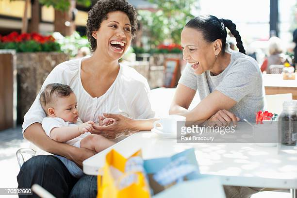 mother, son and friend at outdoor cafe - mom sits on sons lap stock pictures, royalty-free photos & images