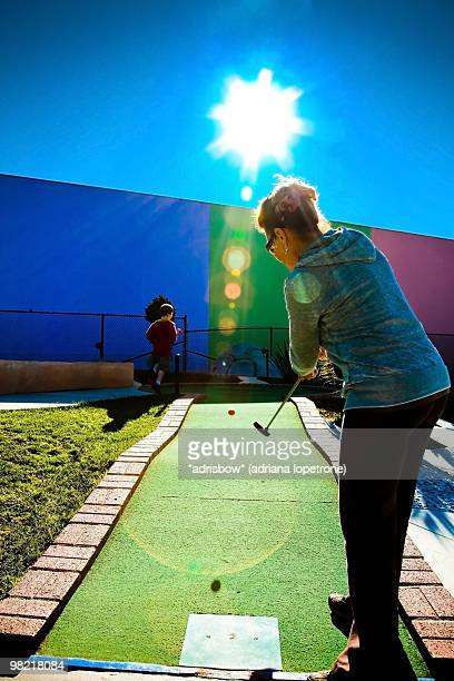 Mother & Son playing miniature Golf on sunny day