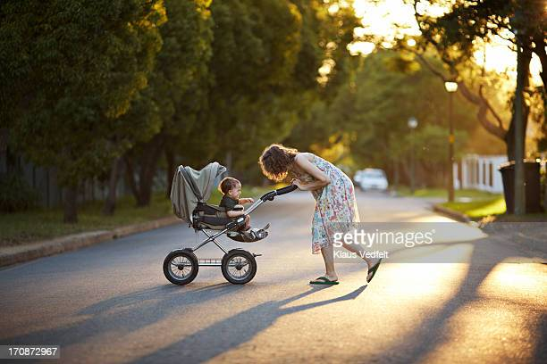 mother & son walking with stroller in the sunset - pushchair stock pictures, royalty-free photos & images