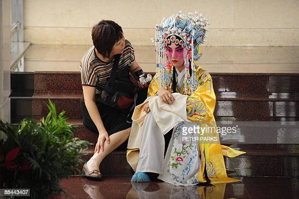 A mother speaks to her daughter as she prepares for an endofyear school performance of Peking Opera an ailing art form the Chinese government is...