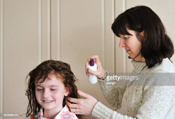 mother spraying child's wet hair with product