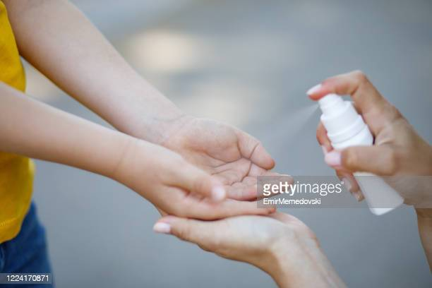 mother spraying hand sanitizer to her little boy's hands - antiseptic stock pictures, royalty-free photos & images