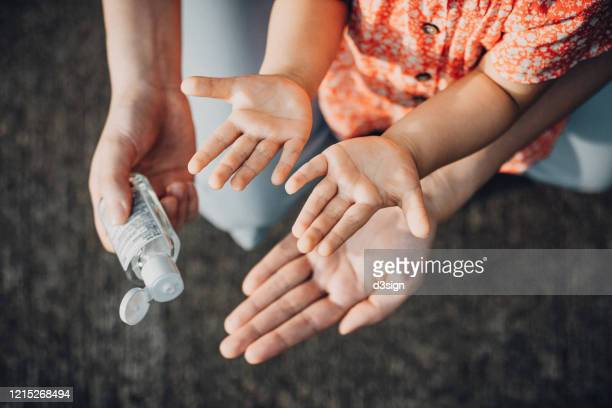 mother squeezing hand sanitizer onto little daughter's hand outdoors to prevent the spread of viruses during the covid-19 health crisis - alcool gel imagens e fotografias de stock