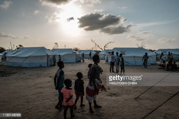 TOPSHOT A mother stand with her children at an evacuation center in Dondo about 35km north from Beira Mozambique on March 27 2019 Five cases of...