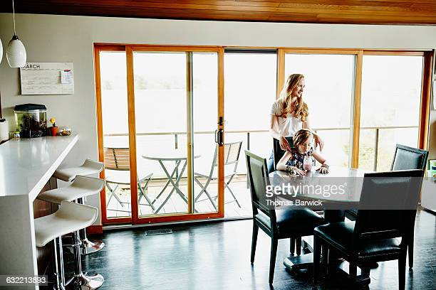 Mother standing behind daughter sitting at table