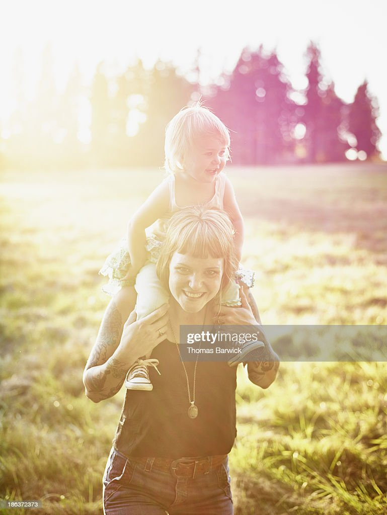 Mother standing holding toddler on shoulders : Stock Photo