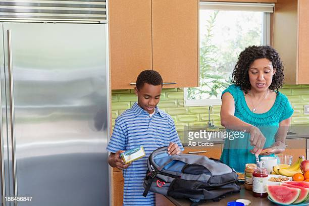 Mother standing in kitchen preparing breakfast for her son (10-11)