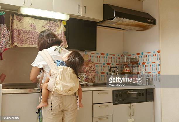 mother standing in the kitchen carrying a baby. - 台所 ストックフォトと画像