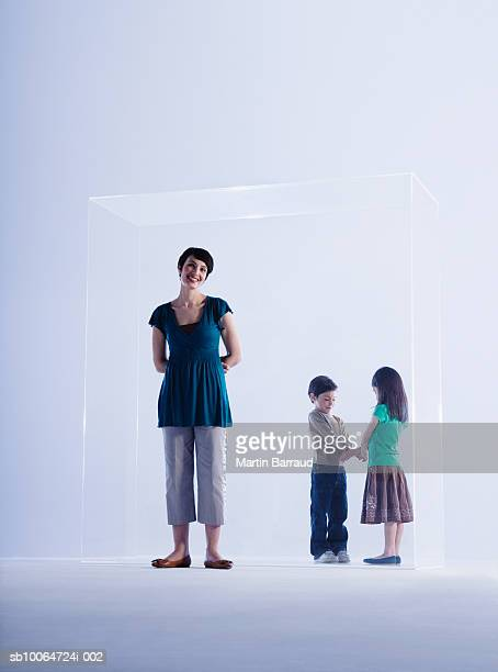 Mother standing outside of glass cabinet, children (6-9) inside