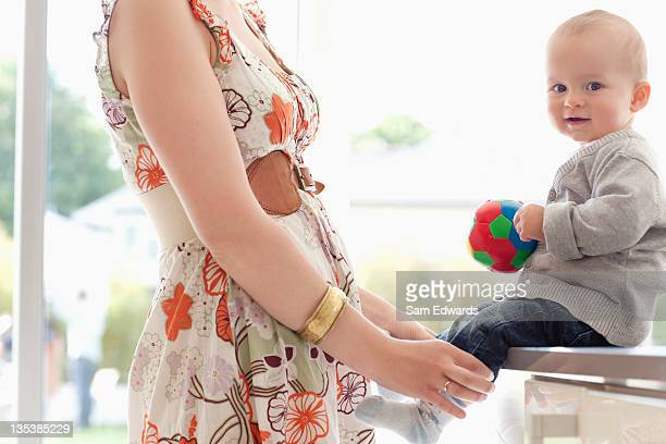 Mother standing with baby holding ball