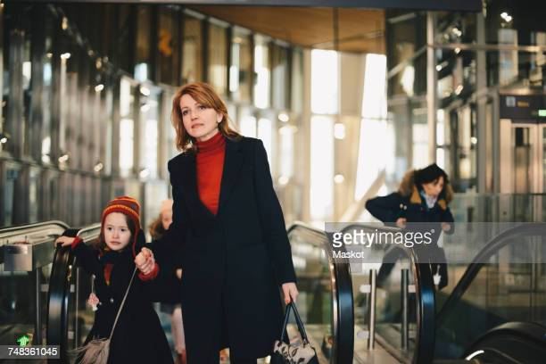Mother standing with daughters against escalators at railroad station