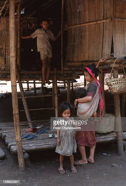 Mother stands in front of her bamboo and leaf hut with her children in a new Karen refugee camp north of the Thai town, Mae Sot. They are recent...