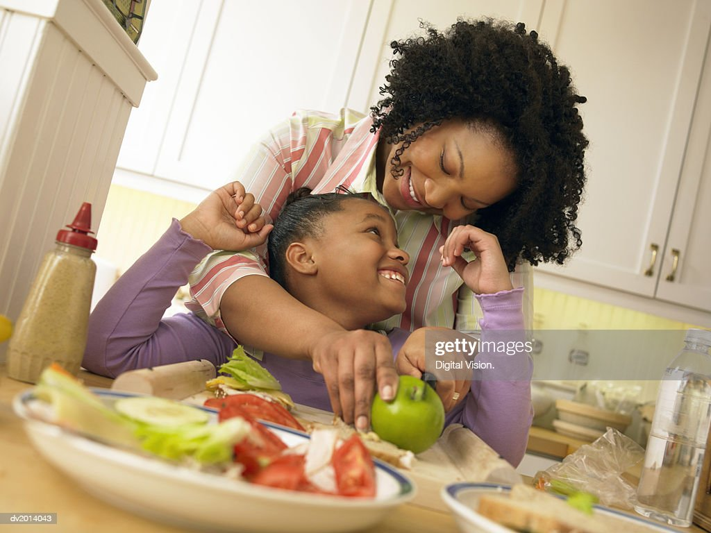 Mother Stands With Her Young Daughter in the Kitchen, Chopping an Apple for Her Lunch : Stock Photo