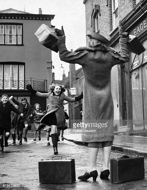 A mother stands with open arms as she greets her daughter in a Sussex village The girl had been evacuated from London at the start of World War II