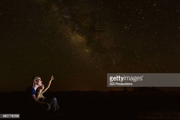 Mother star gazing with young son while he studies constellations