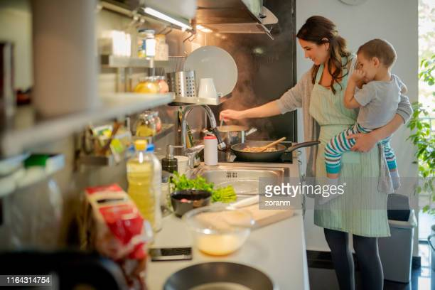 mother stirring food with the toddler on hip - stay at home mother stock pictures, royalty-free photos & images