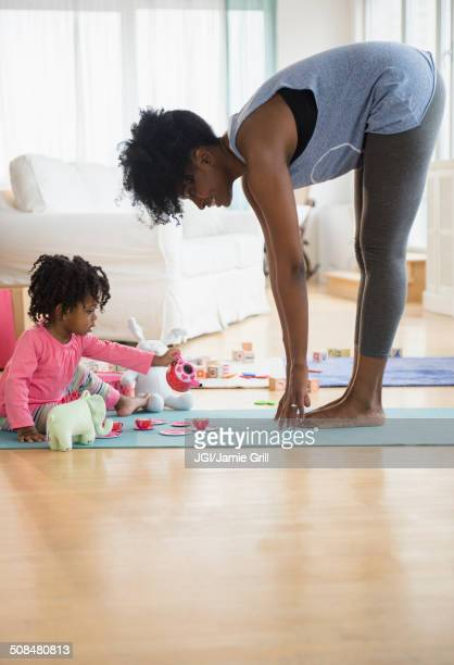mother stretching as daughter plays on yoga mat - daily sport girls stock pictures, royalty-free photos & images
