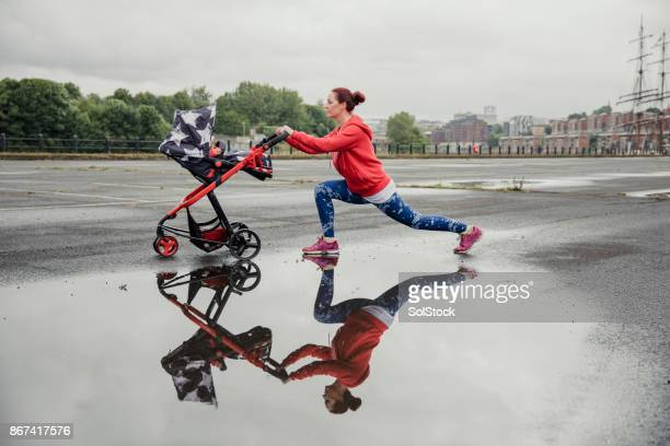 mother stretching with pushchair after run - three wheeled pushchair stock pictures, royalty-free photos & images