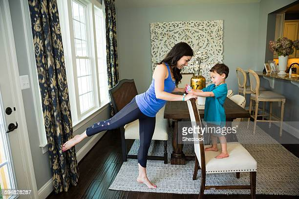 Mother stretching with son in dining room