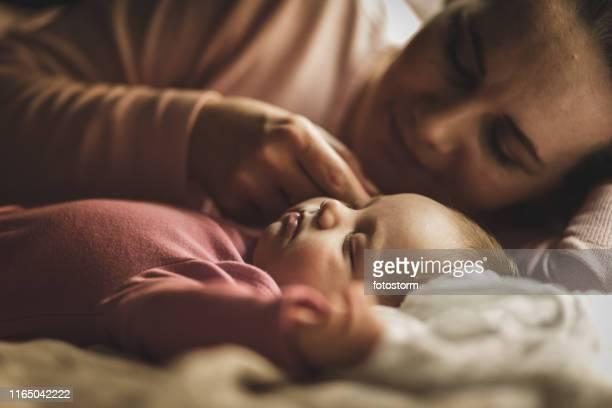 Mother stroking her newborn baby's cheek while cuddling her