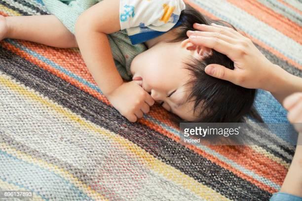 Mother stroking sleeping boy