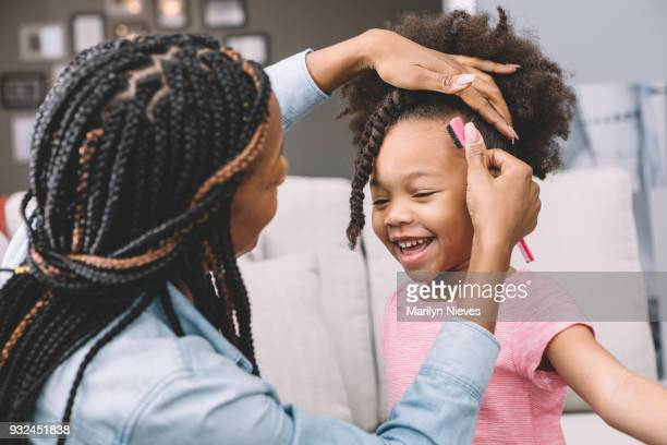 mother styling daughter's curly hair - braided stock pictures, royalty-free photos & images