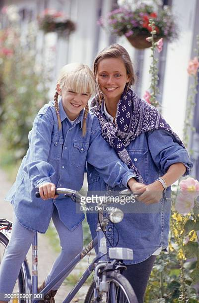 mother supporting girl (12-13 years) riding bike, front view - 30 34 years fotografías e imágenes de stock