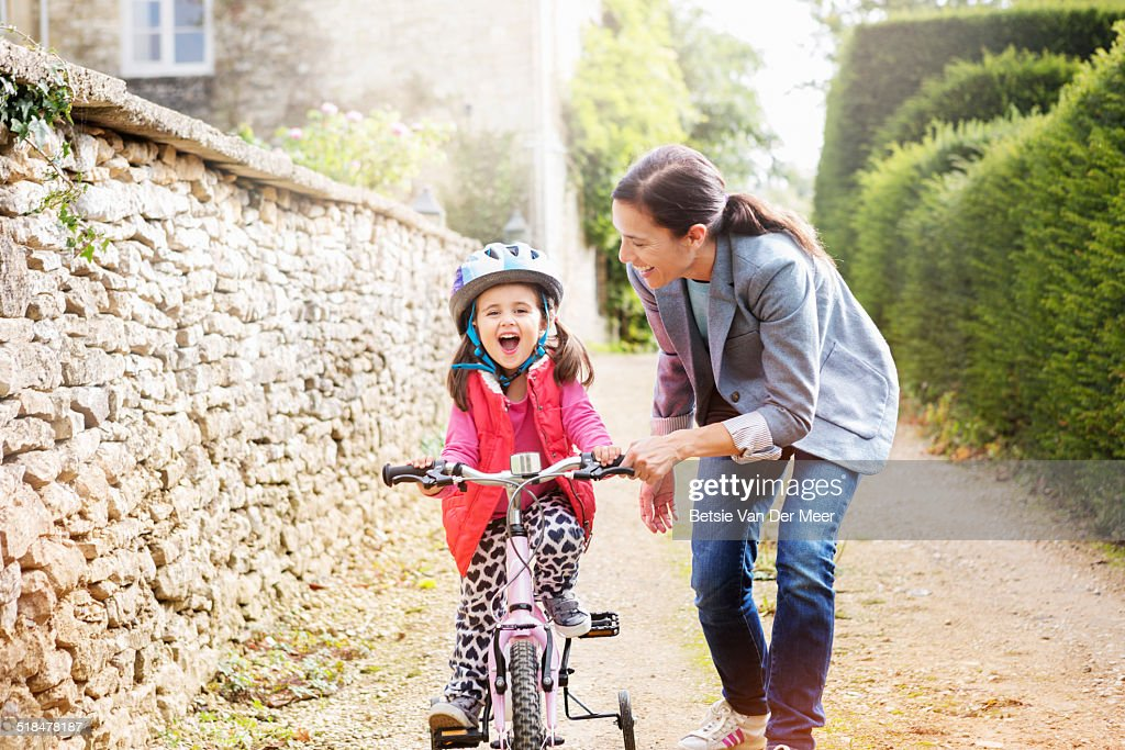 mother supports daughter who is learning cycling. : Stock Photo