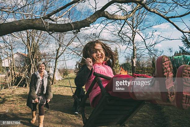 Mother swaying her daughter on a swing