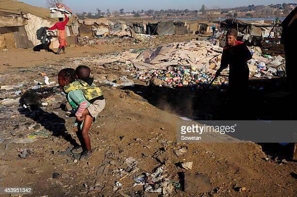 A mother sweeps her yard as her children play nearby on July 21 2014 in Devland South Africa Most children don't go to school because they dont have...