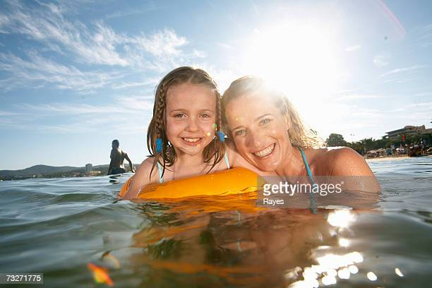 mother swimming with daughter (7-9) in sea - alleinerzieherin stock-fotos und bilder