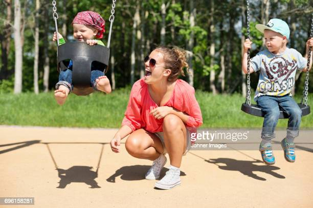 mother swinging baby on playground - bending stock pictures, royalty-free photos & images
