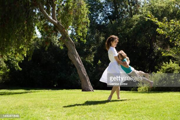 Mother swinging daughter in park