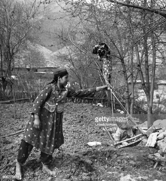 Mother swinging her child near Samarkand in Uzbekistan, Soviet Union, 1970s.