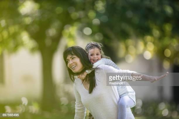 Mother swinging her daughter in garden