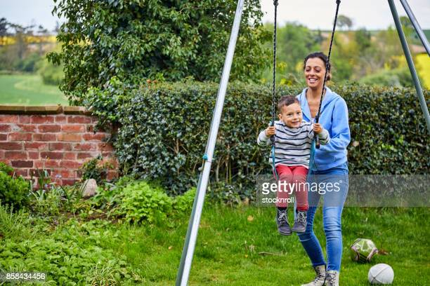 Mother swinging his son in garden