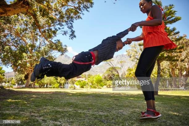 Mother swinging son in park
