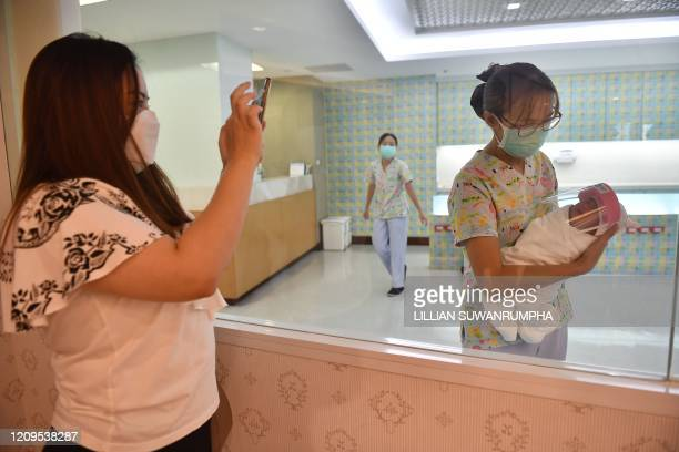 A mother takes a photo of her newborn baby who is wearing a face shield in an effort to halt the spread of the COVID19 coronavirus at Praram 9...