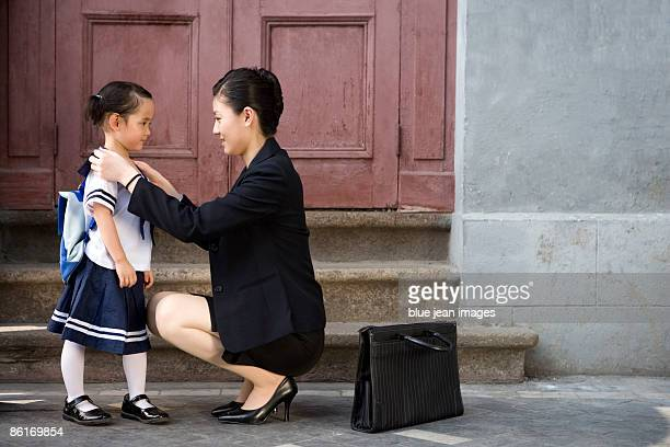 A mother takes her child to school in the morning