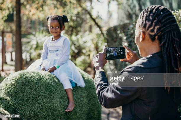 Mother taking a picture of young daughter on grass animal