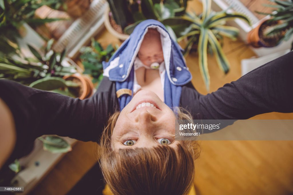 Mother taking a selfie at home with newborn baby in carrier : Stock Photo
