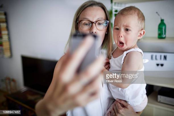 mother taking a selfie with baby daughter - blonde glasses stock-fotos und bilder