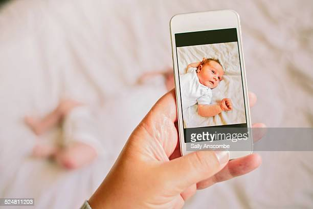 Mother taking a smartphone picture of her baby