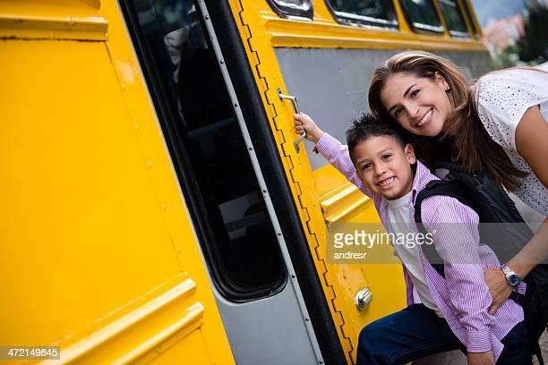 Mutter mit Jungen, der Schulbus