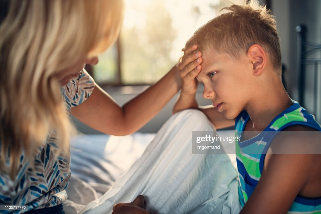 Mother taking care of little boy with a head ache : Stock Photo