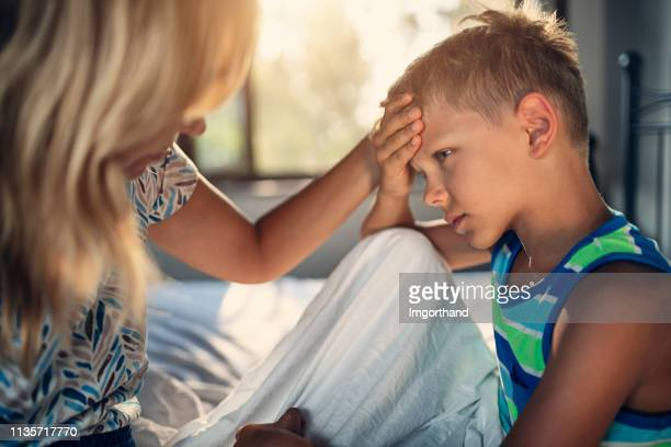 mother taking care of little boy with a head ache - illness stock pictures, royalty-free photos & images