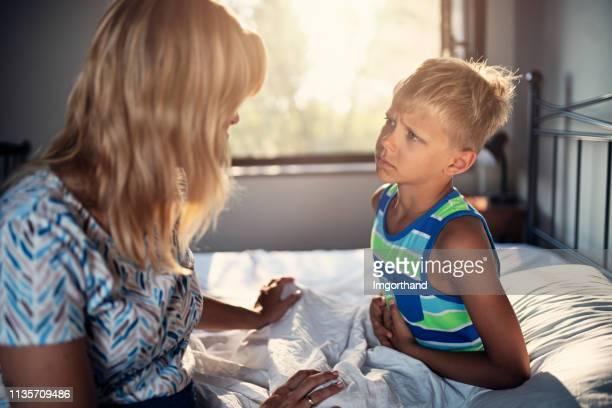 母は胃の痛みで小さな男の子の世話をします - 腹痛 ストックフォトと画像