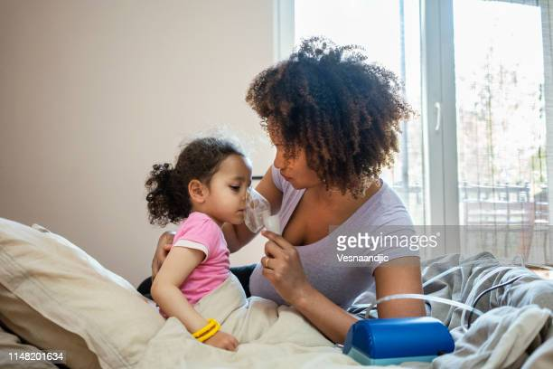 mother taking care on her sick daughter - asthma stock pictures, royalty-free photos & images
