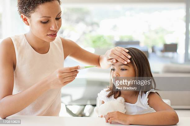 mother taking daughter's temperature - fever stock pictures, royalty-free photos & images